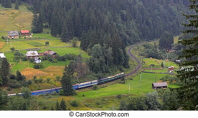 train rides through a village in the mountains