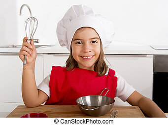 sweet little girl in red apron and cook hat playing chef...