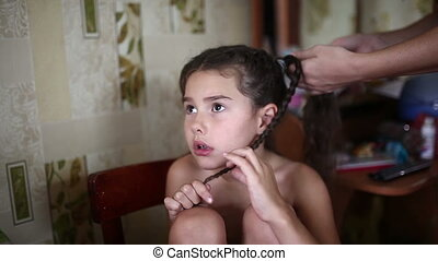 Mom makes daughter female girl hair braid sitting in the...