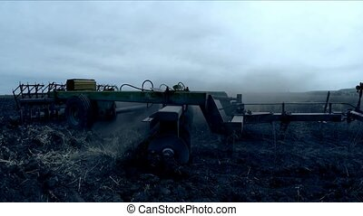 Tractor Plowing Agricultural Field At Dusk - CLOSE UP: Slow...