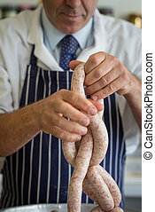 Butcher close up making sausages - Friendly butcher linking...