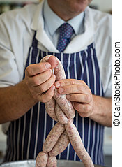 How to link sausages Close up - Friendly butcher linking and...