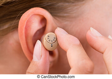 Female Hands Putting Hearing Aid In Ear - Close-up Of Female...