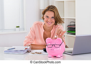 Woman Putting Coin In Piggybank - Happy Woman With Bills...