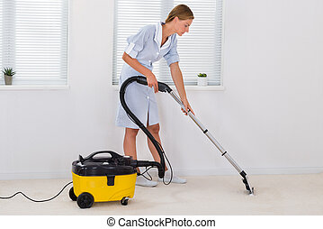 Female Maid Cleaning With Vacuum Cleaner