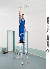 Electrician Installing Ceiling Light - Male Electrician On...