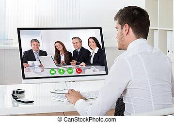 Businessman Videoconferencing On Desktop Computer -...