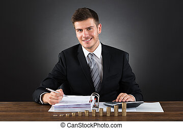 Businessman Doing Accounting At Desk