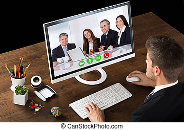 Businessman Videochatting With Colleagues - Young...