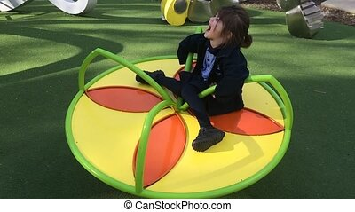 Child play on a carousl playground - Slow motion of a child...