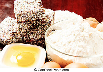Group of Lamingtons on a timber cutting board with food...