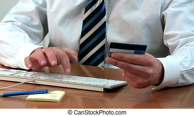 credit card - Businessman holding credit card and typing on...