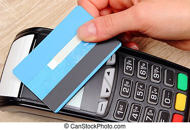 Hand of woman paying with contactless credit card with NFC...