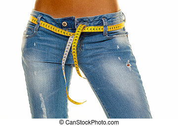 slim woman in jeans with a tape measure