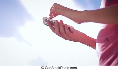 Close up of hands woman using her cell phone on sky...