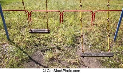 swing swinging with nobody - Old rusty swings on an empty...