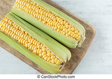 Corncob - Fresh raw corncob on a chopping board