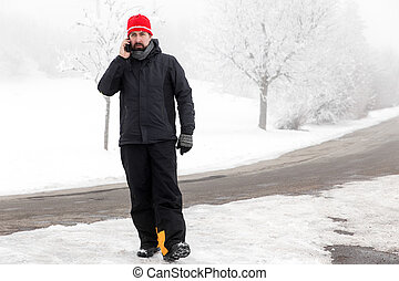Man with mobile phone is walking across a icy street - Man...
