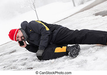 Casualty man is lying on a icy way and calling the ambulance...