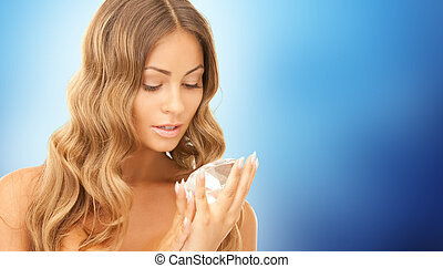 woman holding big diamond over blue background - people,...