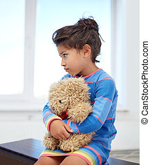 sad little girl with teddy bear toy at home