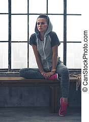 Fit woman sitting on loft gym bench leaning against bent leg...