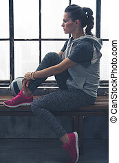 Pensive woman in workout gear looking in profile in loft gym...