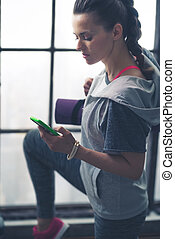 Fit woman in exercise gear in loft gym looking down at phone...