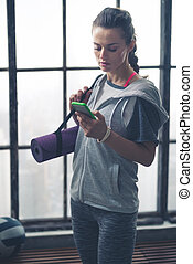 Woman in workout gear in loft gym checking mobile phone -...