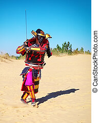 Man in samurai costume with sword running on the sand. Men...