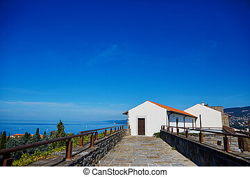 Small white cottage by the sea and blue sky