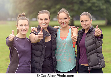 Four Athletic Women Friends Giving Thumbs Up