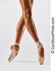 legs in ballet shoes - Ballerina dancing on point in studio