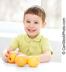 Portrait of a happy little boy with apples