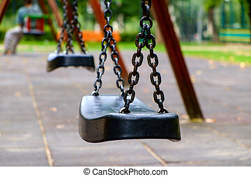 Empty swings on playground - Empty chain swing in playground...