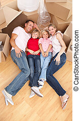 Cheerful family sleeping lying on the floor while moving...