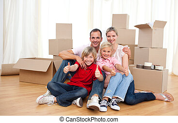 Cheerful family relaxing sitting on the floor while moving...