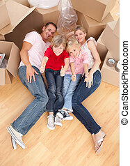 Happy family lying on the floor in their new house