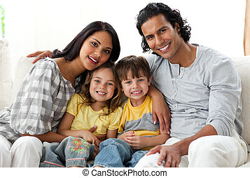 Joyful family watching TV together sitting on a sofa at home...