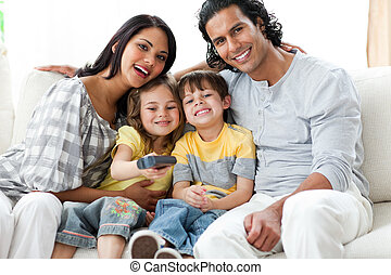Positive family watching TV  together sitting on a sofa at home