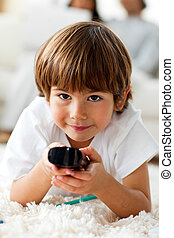 Smiling little boy holding a remote lying on the floor in...