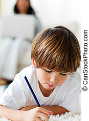 Concentrated little boy drawing lying on the floor