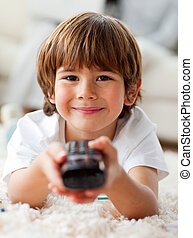 Smiling little boy watching TV lying on the floor in the...