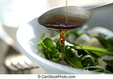 Poring Oil On To Green Salad - Putting oil on the salad with...