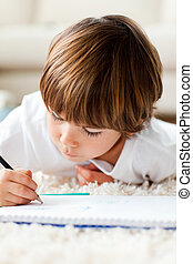 Merry little boy drawing lying on the floor in the living-room