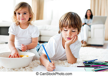 Serious little boy drawing and his sister eating chips lying...