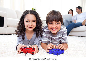 Happy siblings playing video games lying on the floor with...