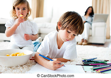 Cute siblings eating chips and drawing lying on the floor