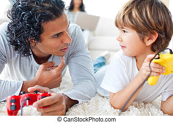 Attentive father with his son playing a video game lying on...