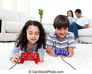 Jolly siblings playing video games lying on the floor with...
